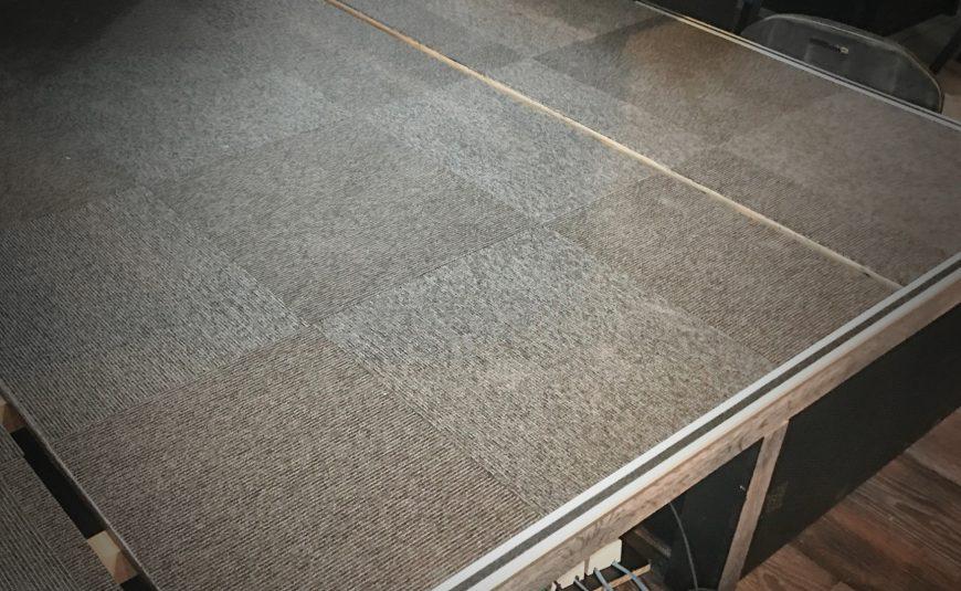 Tæppefliser monteret på lille scene
